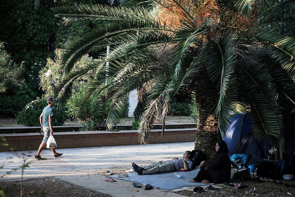 Greece, Athens, July 25th 2015 -Afghan migrants sit outside of their tents at Pedion tou Areos park where hundreds of migrants and refugees mostly from Afghanistan have build a temporary camp, after they arrived in Athens from the Greek islands wishing to continue their journey to central Europe.