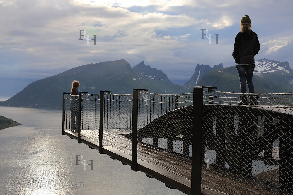 Writer Susan Zimmerman and daughter enjoy view of Bergsfjord from modernistic wooden overlook jutting above valley floor along National Tourist Route on a sunny summer day on Senja Island, Norway.
