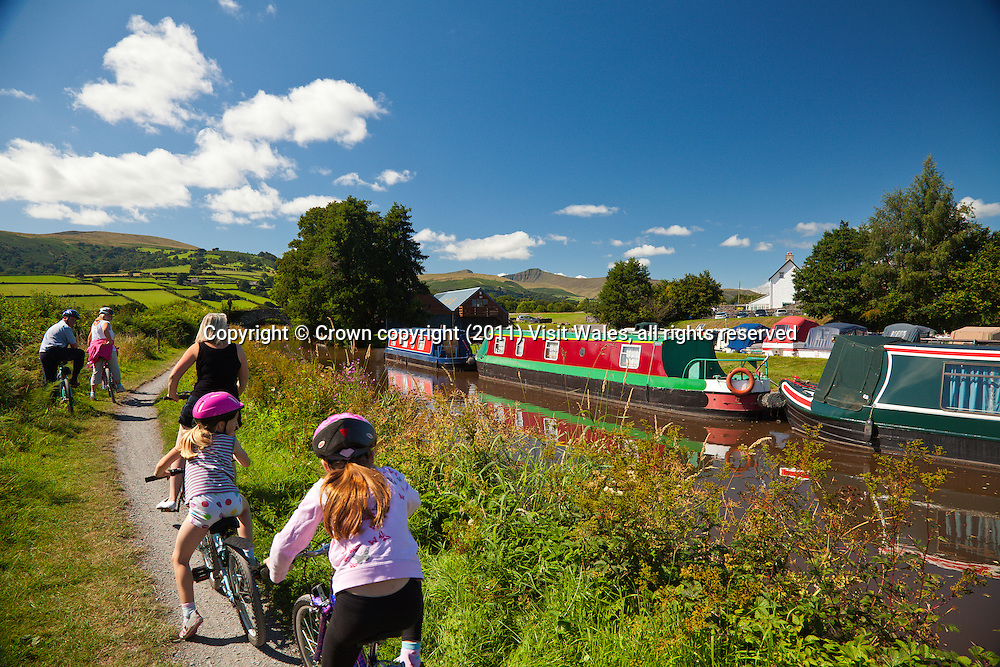 Family cycling along canal towpath at Pencelli<br /> Pen y Fan in background<br /> Monmouthshire and Brecon Canal<br /> Powys<br /> South<br /> Water<br /> Transport<br /> Cycling<br /> Activities and Sports