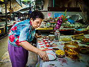 """05 SEPTEMBER 2017 - BANGKOK, THAILAND: A woman sets up her family's Hungry Ghost Day banquets in Bangkok's Chinatown. The Ghost Festival is a Buddhist and Taoist holy day celebrated on the 15th day of the 7th lunar month. It is primarily celebrated in China and Chinese communities outisde China. In Thailand, it's celebrated in Thai-Chinese communities in Bangkok, Phuket and Chiang Mai.  On that day ghosts and spirits, including those of the deceased ancestors, come out from the lower realm to visit the living. Families prepare elaborate banquets for the spirits and burn """"ghost money"""" for the spirits to use in the other realm. It is a day for venerating dead relatives.      PHOTO BY JACK KURTZ"""