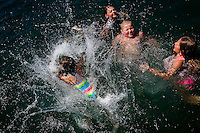 Karlee Marrero, 8, dives into the water at Honeysuckle Beach and splashes her friends Emily Duncan, 10, right, Andrew Johnson, 9, and Kari Greenbank, 10, during an outing Thursday to Hayden Lake with the Quest Summer Camp from the Coeur d'Alene Church of the Nazarene.
