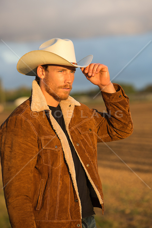 cowboy looking at the sunset on a ranch