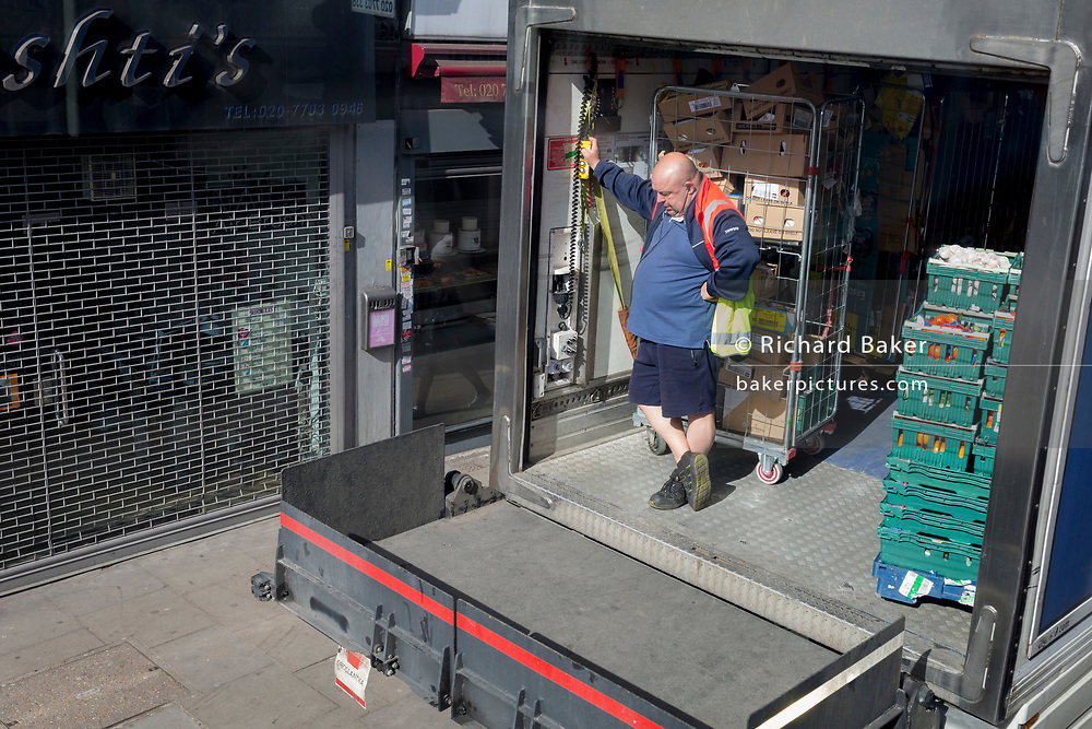 A supermarket delivery driver raises his hydraulic tailgate at the rear of his lorry while offloading supermarket caged goods while being parked on the Walworth Road, on 25th March 2019, in London, England.