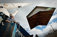 JEROME A. POLLOS/Press..Pat Steele, with Coeur d'Alene Crane Service, moves the roof to a 13x16-foot shed that was donated to Fresh Start in Coeur d'Alene.