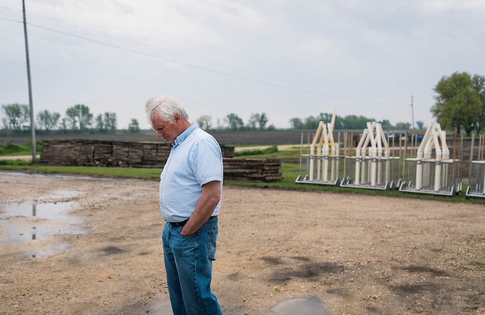 Farmer Ken Ries looks down at the ground outside his hog farm in Ryan, Iowa, U.S. May 18, 2019. Picture taken May 18, 2019.  REUTERS/Ben Brewer