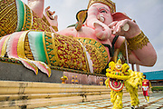 "29 SEPTEMBER 2012 - NAKORN NAYOK, THAILAND:  Thai Chinese style Lion dancers perform in front of a stature of Ganesh during observances of Ganesh Ustav at Wat Utthayan Ganesh, a temple dedicated to Ganesh in Nakorn Nayok, about three hours from Bangkok. Many Thai Buddhists incorporate Hindu elements, including worship of Ganesh into their spiritual life. Ganesha Chaturthi also known as Vinayaka Chaturthi, is the Hindu festival celebrated on the day of the re-birth of Lord Ganesha, the son of Shiva and Parvati. The festival, also known as Ganeshotsav (""festival of Ganesha"") is observed in the Hindu calendar month of Bhaadrapada, starting on the the fourth day of the waxing moon. The festival lasts for 10 days, ending on the fourteenth day of the waxing moon. Outside India, it is celebrated widely in Nepal and by Hindus in the United States, Canada, Mauritius, Singapore, Thailand, Cambodia, Burma , Fiji and Trinidad & Tobago.     PHOTO BY JACK KURTZ"
