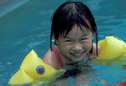 Young girl learning to safely swim in pool