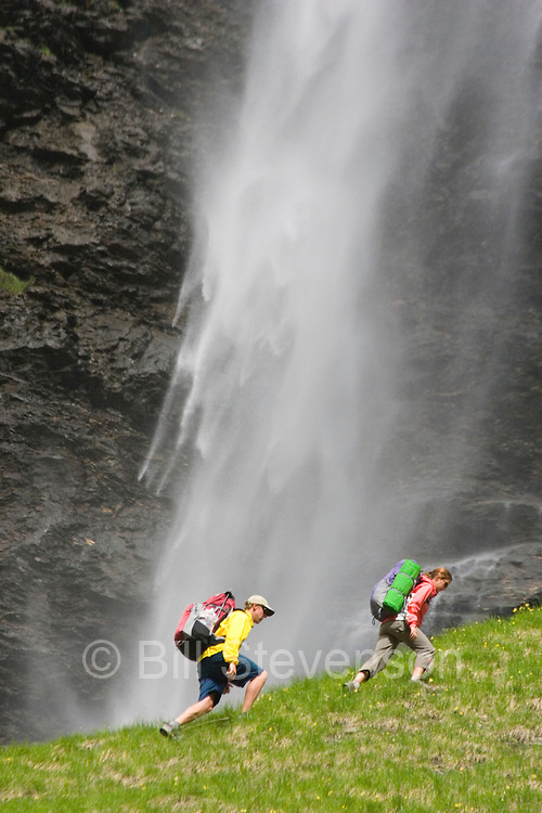 A picture of a couple hiking beneath of a waterfall in Fer a Cheval France