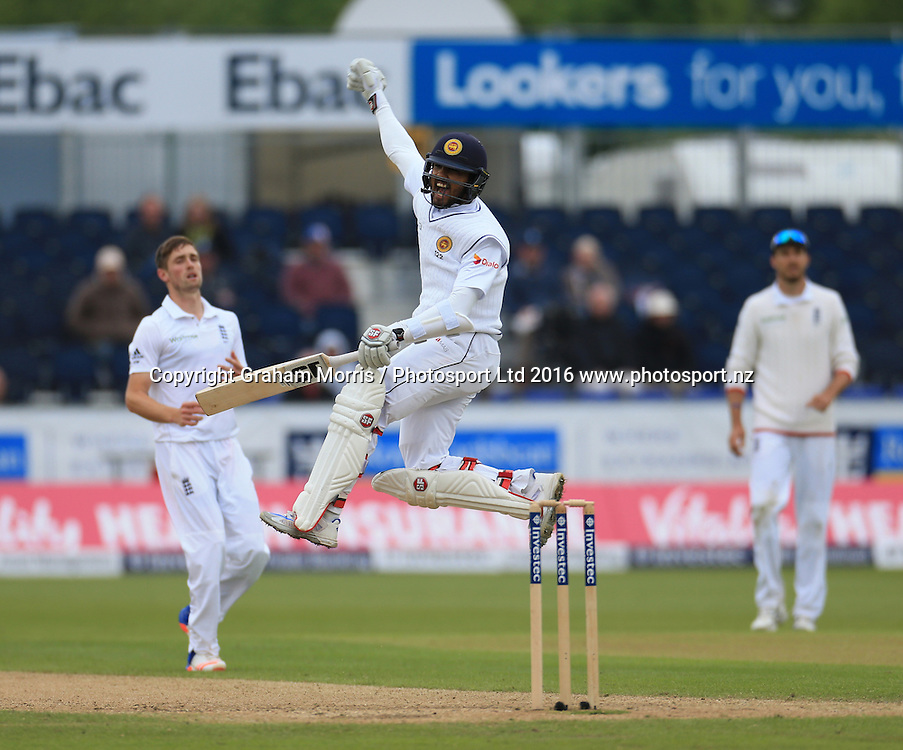Dinesh Chandimal celebrates his century (watched by bowler Chris Woakes, left, and Steven Finn) during the second Investec Test Match between England and Sri Lanka at Chester-le-Street, Durham. Photo: Graham Morris/ Photosport.nz