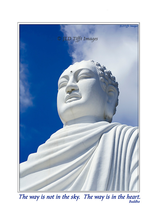 Oversize (24 meters high with base) seated Buddha statue at Long Son Pagoda, near Nha Trang, Vietnam, seen against a bright blue sky and shapely white clouds.  The image shows only the bust and head, radiating calm.