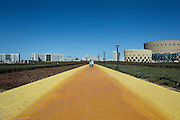 Two women walk on a golden sidewalk in the New City of Kangbashi, or Ordos in Inner Mongolia.