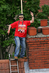 LIVERPOOL, ENGLAND - THURSDAY, MAY 26th, 2005: A Liverpool fan with an Elvis wig stands on his chimney top to get a better view of the players as they parade the European Champions Cup on on open-top bus tour of Liverpool in front of 500,000 fans after beating AC Milan in the UEFA Champions League Final at the Ataturk Olympic Stadium, Istanbul. (Pic by David Rawcliffe/Propaganda)