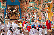 Monks praying in Tay Ninh 's Cao Dai Temple, Vietnam, Asia