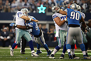 Dallas Cowboys quarterback Tony Romo (9) throws a pass as he gets hit by Detroit Lions defensive end Ezekiel Ansah (94) during the NFL week 18 NFC Wild Card postseason football game against the Detroit Lions on Sunday, Jan. 4, 2015 in Arlington, Texas. The Cowboys won the game 24-20. ©Paul Anthony Spinelli