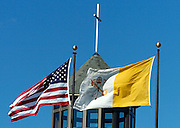 An American and papal flag hang outside of a Catholic church. (Sam Lucero photo)