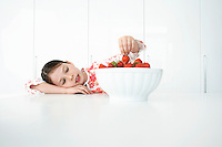 Girl (7-9) leaning on table and picking strawberries from bowl