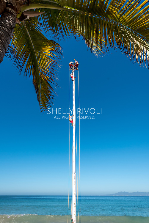 The Pampantla Flying Birdmen climb to the top of a tall pole before performing on the Puerto Vallarta Malecon. The Mexican street performers wear traditional costumes and and famously spin upside down from the pole.