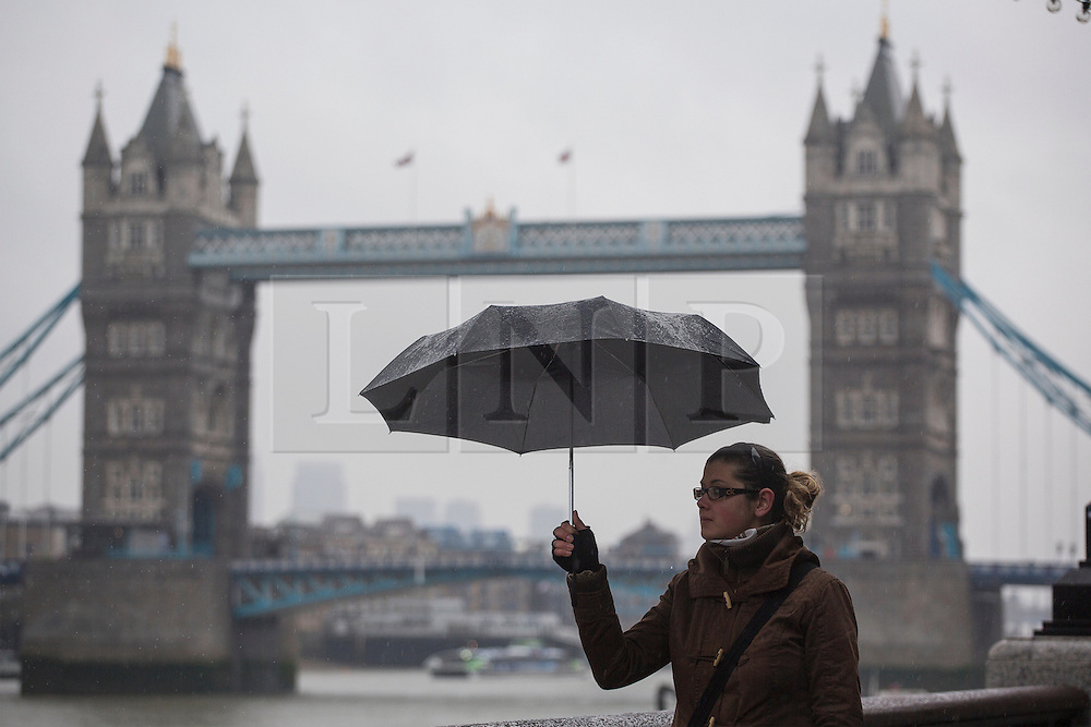 © licensed to London News Pictures. London, UK 14/12/2012. People walking under rain outside City Hall on 14/12/12. Photo credit: Tolga Akmen/LNP