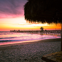 San Clemente pier California sunset photo. Inlcudes a straw tiki umbrella and beautiful purple and orange colors along the Southern California coastline. San Clemente is a popular coastal city in Orange County in the United States of America. Copyright ⓒ 2017 Paul Velgos with all rights reserved.