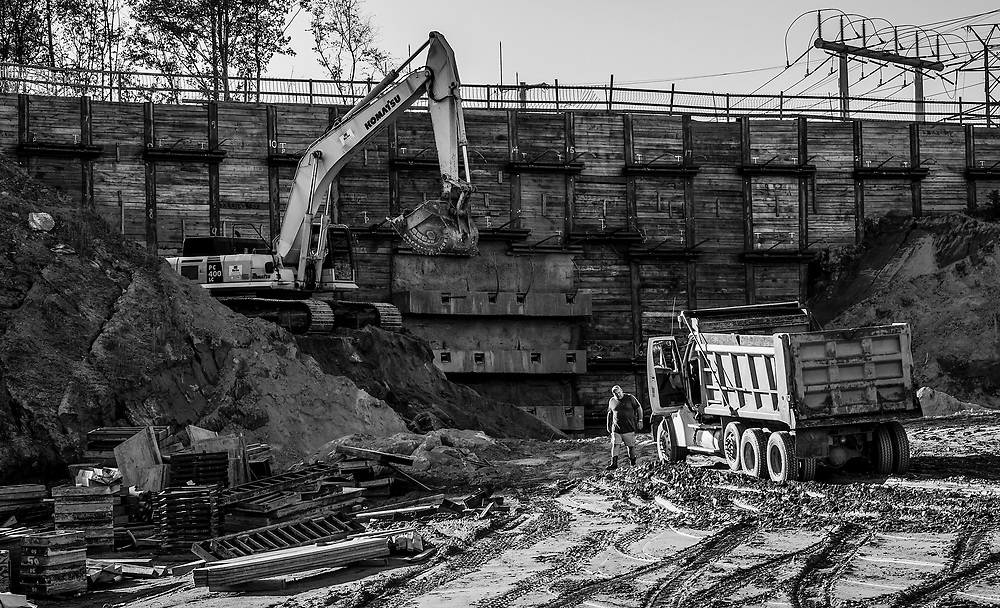 The last truck of day prepares to leave this construction site.  Earth is being moved away from the wall that supports a train track above.  I suspect a new bridge is being built to allow traffic to pass under.  The composition features a busy array of shapes & textures.