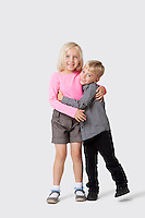 Portrait of happy young siblings hugging over white background