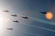 Air show planes off into the sun