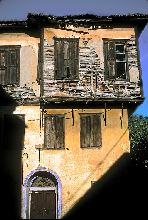 Derelict Ayvalik house showing projecting upper floor walls deteriorating, showing lath, plaster, glass, all brokenand decaying.  Lower story is finished so that one might think it occupied.