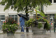A person walks south along N. Patterson Blvd next to Fifth Third Field while smokers huddle under near a doorway as the rains fall in downtown Dayton, Wednesday, June 4, 2008.