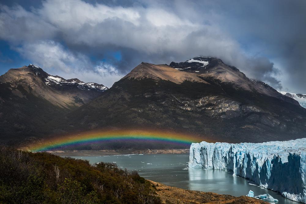 Rainbow stretching over Perito Moreno Glacier in Los Glaciares National Park, Argentina