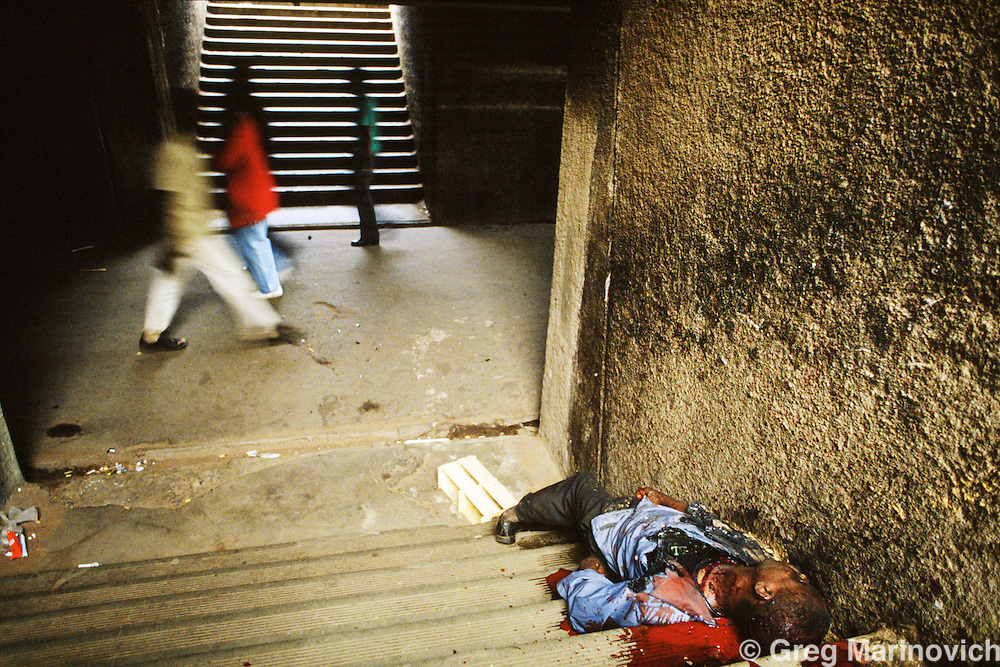 Dube, Soweto, 1994, South Africa: Commuters walk past a man killed in a train subway in Soweto. 1994.