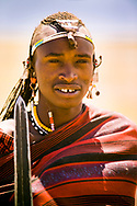 Portrait of Maasai tribesman holding a spear in the Ngorongoro Crater, Tanzania.  The Maasai are an indigenous group of semi-nomadic people located in Kenya and northern Tanzania.  They are among the most well-known of African ethnic groups internationally due to their distinctive customs, dress and residence near the many game parks in East Africa.