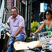NLD/Amsterdam/20100821 - Spotjournalist Tom Egbers en partner Janke Dekker fietsend door Amsterdam