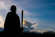 Africa, Tanzania, A silhouette of a Maasai Man with traditional staff in hand at sunset an ethnic group of semi-nomadic people