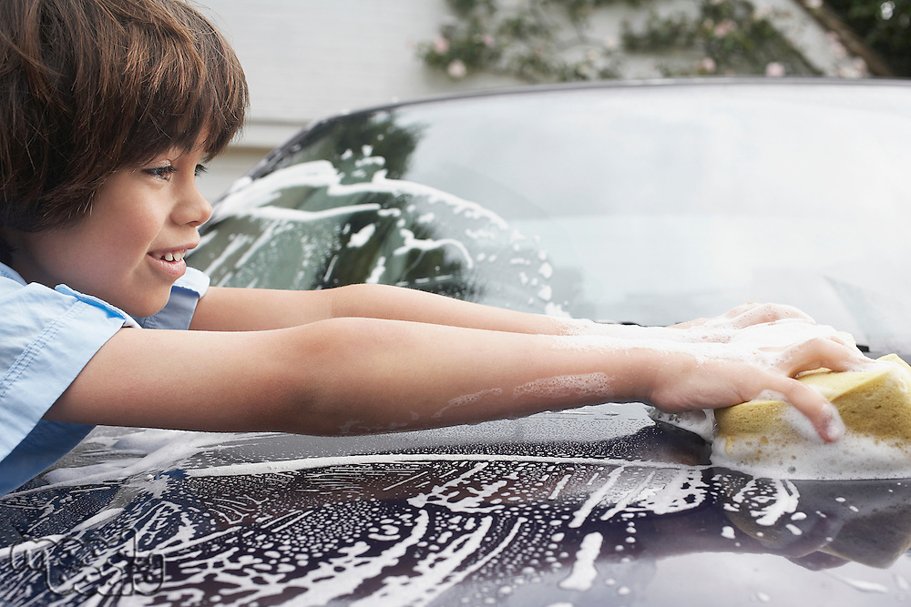 Young boy (7-9) washing car with sponge side view