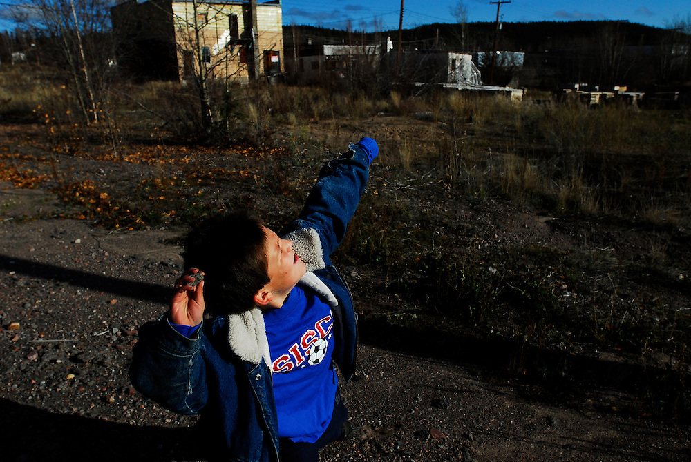 URANIUM CITY, SK - 11/10/08 -  Seven-year-old Riley finds out how far he can toss stones in an empty yard in 'downtown' Uranium City Saskatchewan.