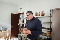 BARCELLONE POZZO DI GOTTO (ME), ITALIA - 20 FEBBRAIO 2015: Fabio Conti pulisce con una spugna una brocca  di terracotta nel laboratorio di ceramica della Casa di Solidarietà e di Accoglienza a Barcellona Pozzo di Gotto il 20 febbraio 2015.