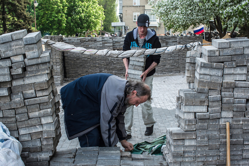 DONETSK, UKRAINE - MAY 4: Men use bricks lifted from the sidewalk to build barricades outside the regional administration building, which is occupied by pro-Russian protesters, on May 4, 2014 in Donetsk, Ukraine. Cities across Eastern Ukraine have been overtaken by pro-Russian protesters in recent weeks, leading the Ukrainian military to respond with force in some areas. (Photo by Brendan Hoffman for The Washington Post)