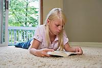 Girl (7-9) lying on carpet reading book