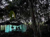 A FARC rebel sits on a cot in her tent in a camp in the remote Putumayo region of Colombia, on December 9, 2016. (Photo/Scott Dalton)