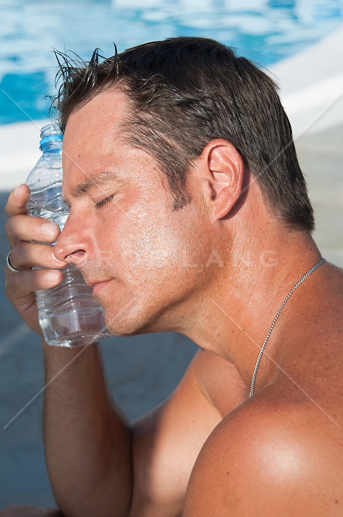 man with a water bottle cooling himself off
