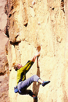 Young man bouldering at Smith Rock State Park, Oregon, USA.