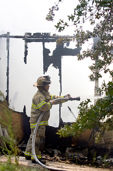 Lee Williams of the Culkin Volunteer Fire Department fights a structure fire at 276 Woodham Road on Wednesday, July 6, 2011. The house is owned by the recently deceased Shirley Faye Humphries Woodham who was survived by her two sons Robert Humphries of Brandon and Daniel Humphries of Vicksburg. No one was injured in the blaze, and volunteer fire department coordinator Kelly Worthy said today the cause of the fire is still under investigation. (Bryant Hawkins/The Vicksburg Post)