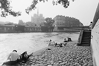 1990, Paris, France --- Couples and others relax on an embankment of the Seine on Ile St.-Louis on a sunny day. Notre Dame cathedral can be seen across the water, on the Ile de la Cite. --- Image by © Owen Franken/CORBIS - Photograph by Owen Franken