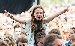 © Licensed to London News Pictures. 13/06/2015. Isle of Wight, UK.  Young girls on their dads shoulders watching Ella Eyre perform at Isle of Wight Festival 2015 on Saturday Day 3.  Yesterday suffered torrential rain all afternoon and evening, after a first day of warm sun.  This years festival include headline artists the Prodigy, Blur and Fleetwood Mac.  Photo credit : Richard Isaac/LNP