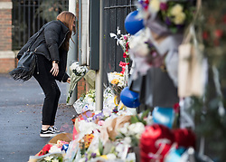 © Licensed to London News Pictures. 28/01/2018. London, UK. A young woman places flowers at the scene where three teenage pedestrians were killed near a bus stop in Hayes, West London after a black Audi collided with them. Named locally as Harry Rice, Josh Kennedy and George Wilkinson, the three teenagers were hit on Friday night  close to the M4 Junction 4. A 28-year-old man has been arrested and a police are currently looking for a  second man believed to have been in the Audi.. Photo credit: Ben Cawthra/LNP