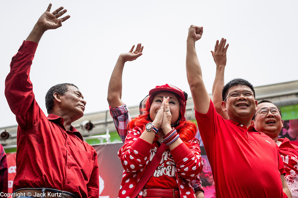 """19 MAY 2013 - BANGKOK, THAILAND:  Red Shirt leaders, including DARUNEE KRITTABOONYALAI, a well known Thai society matron and member of the ruling elite, take the stage during a Red Shirt rally in Ratchaprasong Intersection honoring Red Shirts killed by the Thai army in 2010. Kritboonyalai is a so-called """"HiSo"""" or High Society. Most of the Red Shirts are populists and members of the Thai working class and it's unusual for them to have HiSo supporters. More than 85 people, most of them civilians, were killed during the Thai army crackdown against the Red Shirt protesters in April and May 2010. The Red Shirts were protesting against the government of Abhisit Vejjajiva, a member of the opposition who became Prime Minister after Thai courts ruled the Red Shirt supported government was unconstitutional. The protests rocked Bangkok from March 2010 until May 19, 2010 when Thai troops swept through the protest areas arresting hundreds.    PHOTO BY JACK KURTZ"""