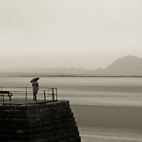 A woman standing all alone on a jetty holding an umbrella