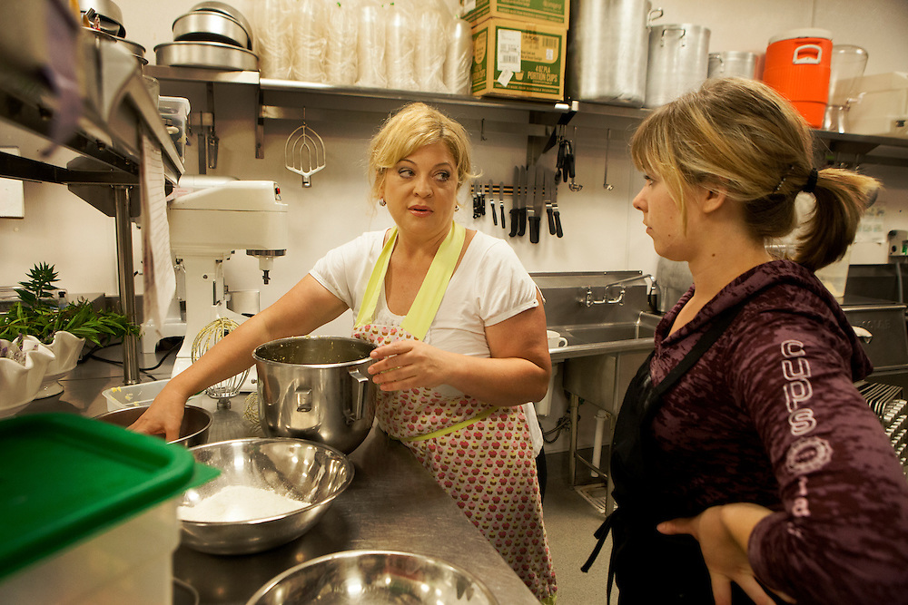 Michelle Ciccarelli Lerach works alongside baker Hope Trevino in the kitchen at Cups, a cupcake shop she owns in La Jolla. She's a vehement supporter of Proposition 37.