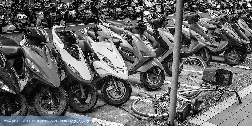 An army of scooters stand over a lone fallen bicycle. Taipei, Taiwan.