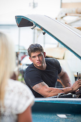sexy auto mechanic taking a break from working on a classic car to look at a blonde girl